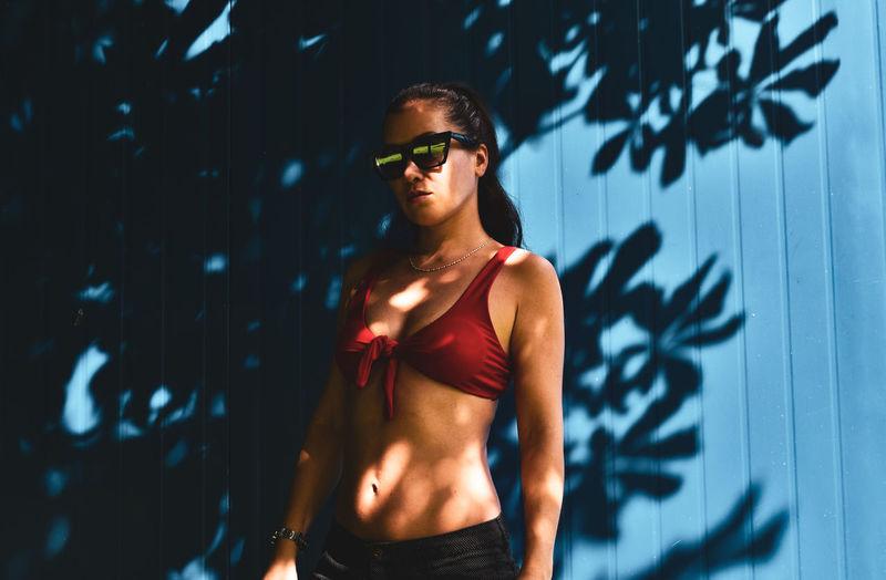Woman wearing bikini top standing by wall