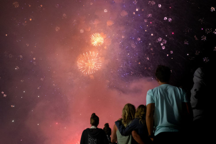 Rear view of people looking at fireworks against sky at night