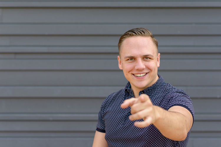 Portrait of smiling man pointing at camera while standing against wall