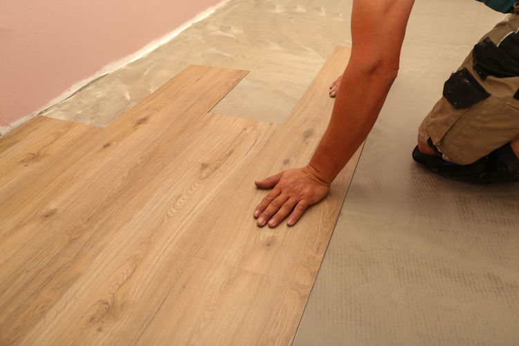 Midsection of carpenter installing laminate on floor
