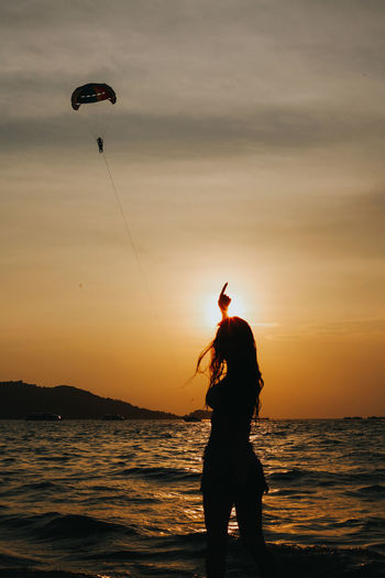 Girl pointing at the paraglide in the sky at the sunset in summer. silhouette of people concept.