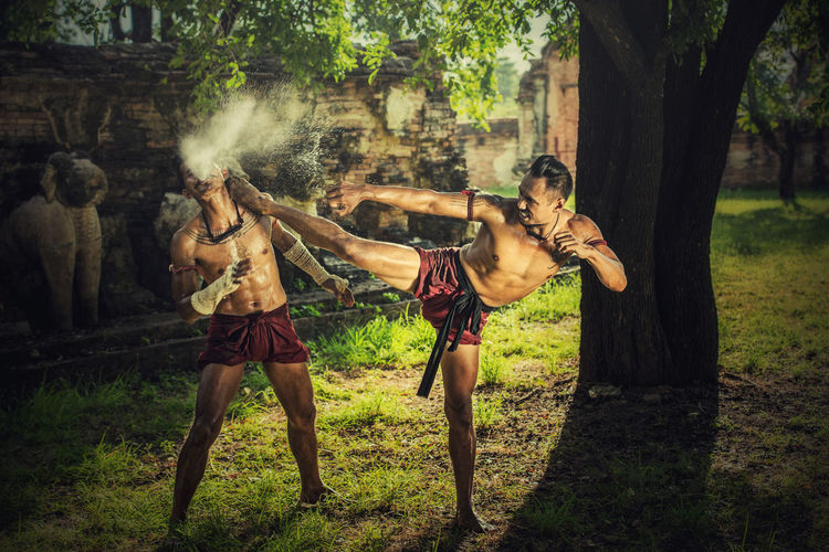 Martial arts of Muay Thai,Thai Boxing at Ayutthaya Historical Park in Ayutthaya, Thailand Combat Ayutthaya Boxing Thailand Warrior Adult Battle Day Nature Outdoors People Real People Riot Traditional Tree Weapon Young Adult