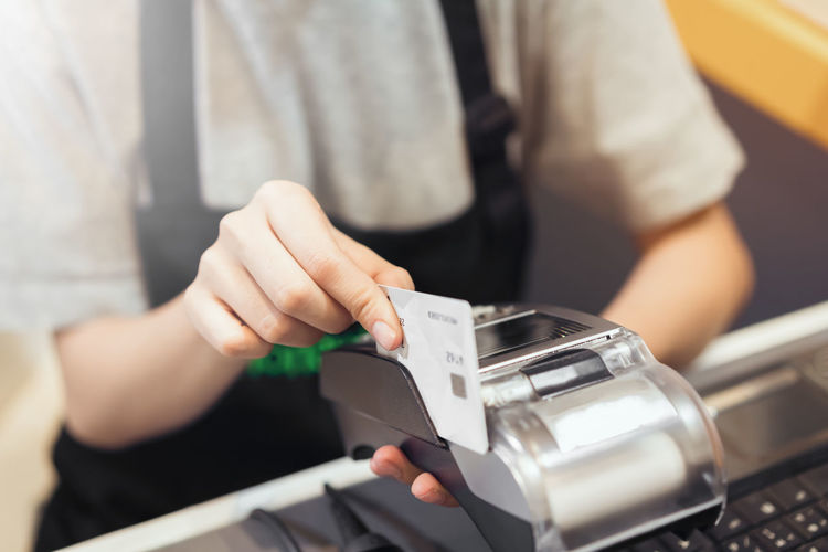Midsection of cashier swiping the credit card