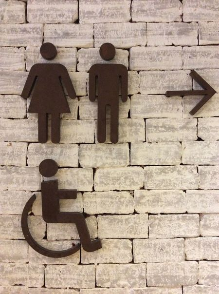 Bangkok Thailand. Signage Men Women Disabled Arrow pointing right Restroom Signage Interior Brick Wall White