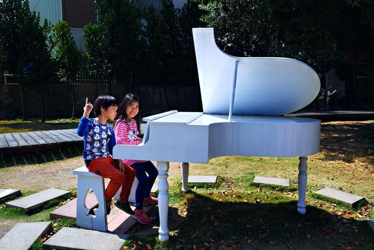 Boy and girl playing piano while sitting on bench against trees