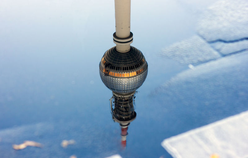 High Angle View Of Fernsehturm Against Sky Reflecting In Puddle