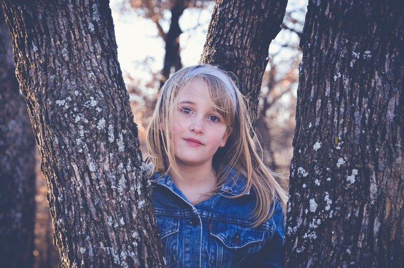 Blond Hair Child Childhood Children Only Day Eye Color Front View Girls Headshot Nature One Girl Only One Person Outdoors People Portrait Tree Tree Trunk
