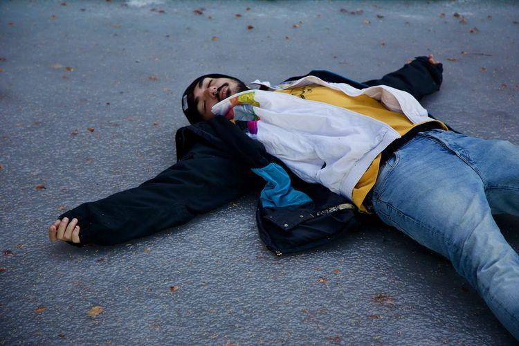Man lying down on road