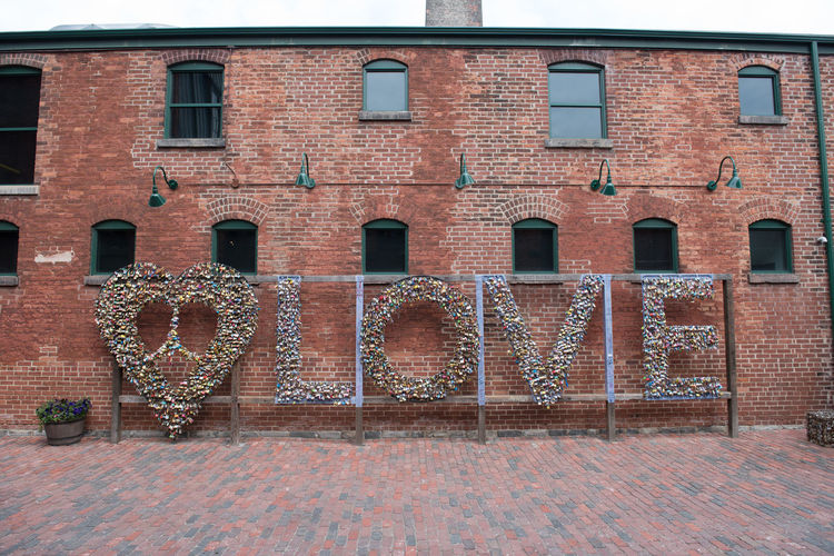 A love sign in Canada. Brick Wall Love Positive Wall Architecture Brick Brick Wall Building Building Exterior Built Structure City Communication Day Heart Lighting Equipment Nature No People Outdoors Pride Residential District Sign Text Wall Wall - Building Feature Western Script Window