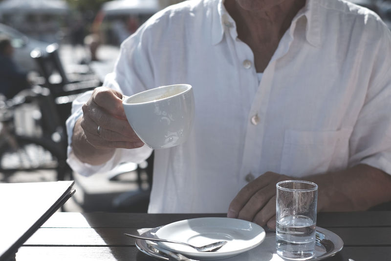 Midsection of man holding drink on table