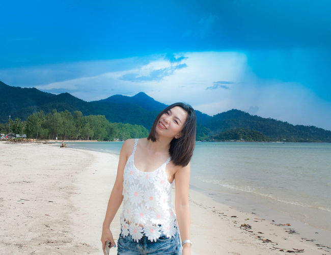 Portrait of smiling mid adult woman standing on beach against blue sky