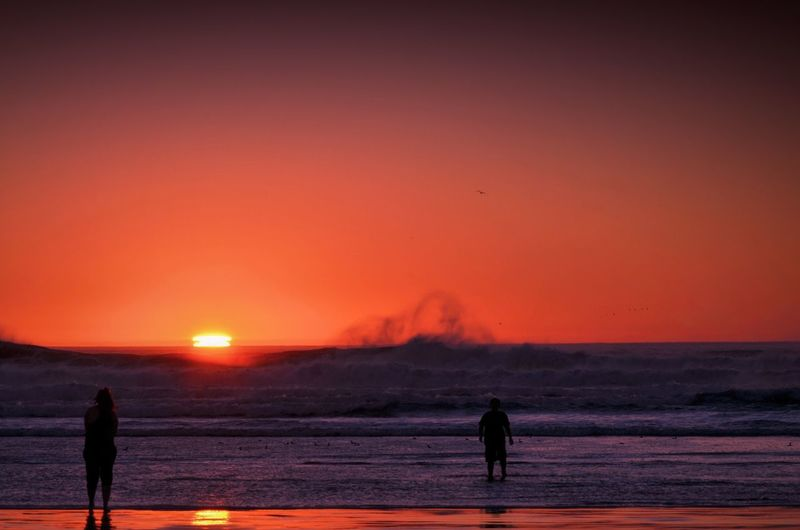 Two Silhouette People Walking On Beach At Sunset