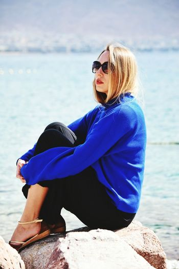 Woman wearing sunglasses sitting on rock by sea against sky
