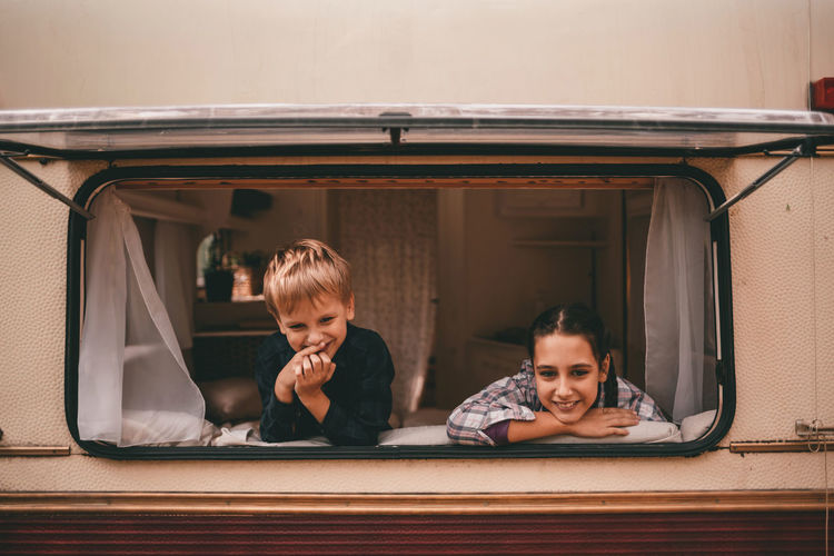 Two happy smiling kids brother and sister look out the window of the camping trailer