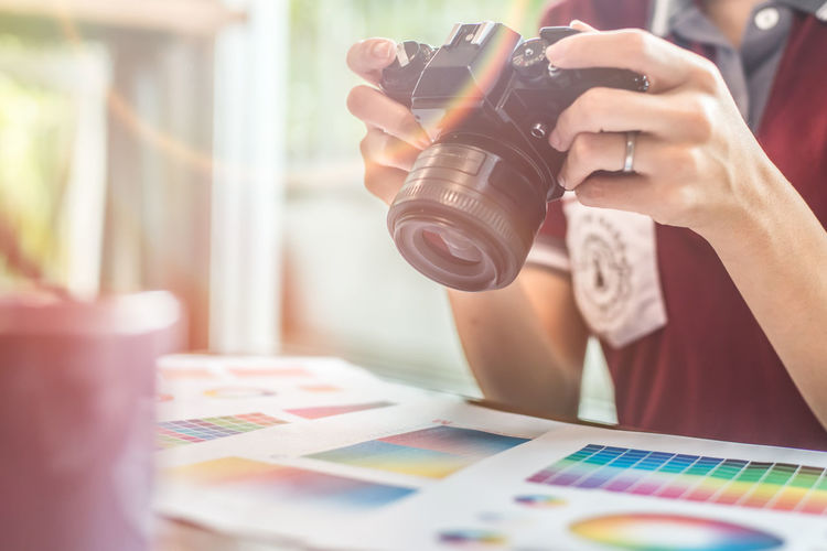 Midsection of woman photographing color swatch in office