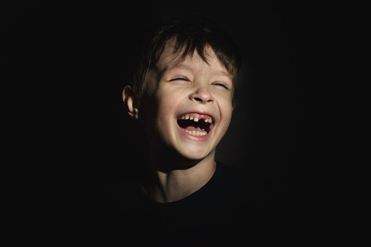 Portrait of boy against black background