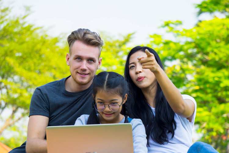 Young family with children having fun in nature park Bonding Boys Casual Clothing Childhood Communication Connection Daughter Day Family Family With One Child Father Focus On Foreground Front View Laptop Leisure Activity Lifestyles Mid Adult Men Outdoors Real People Sitting Son Technology Togetherness Using Laptop Wireless Technology