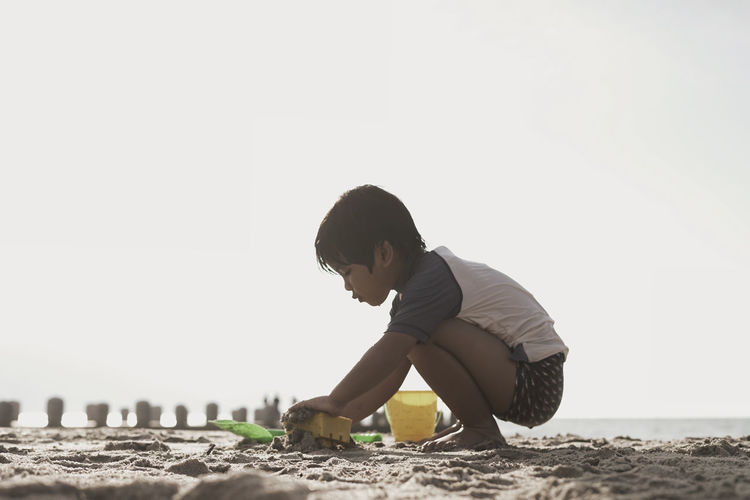Side view of boy playing with toys at beach