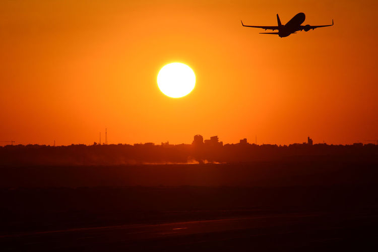 Air Vehicle Airplane Aviation Beauty In Nature Environment Flying Landscape Mid-air Mode Of Transportation Motion Nature No People on the move Orange Color Outdoors Scenics - Nature Silhouette Sky Sun Sunset Transportation