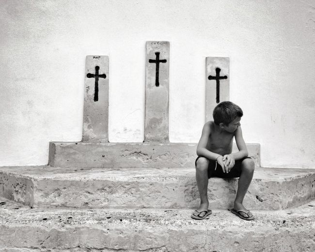 Shirtless Boy Sitting On Steps Against Cross On Wall