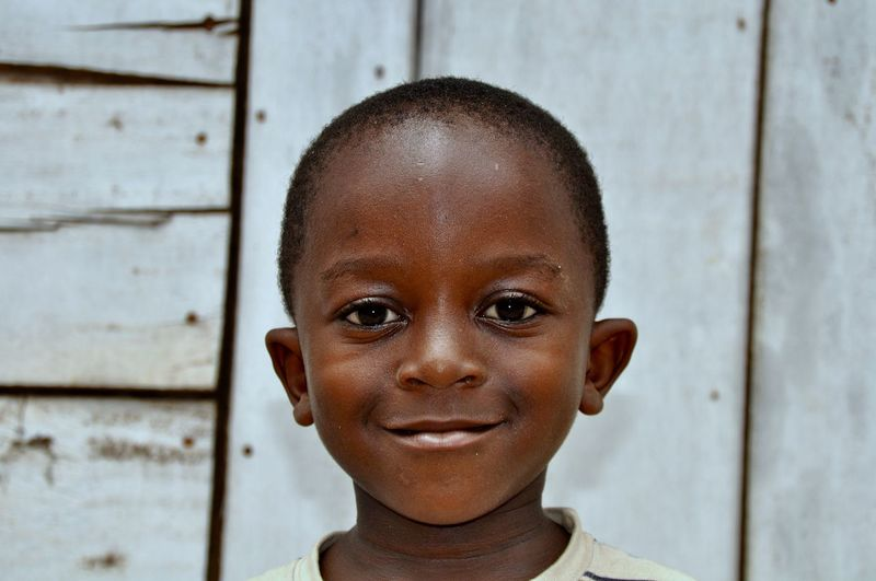 Close-Up Portrait Of Smiling Boy Against Wooden Wall