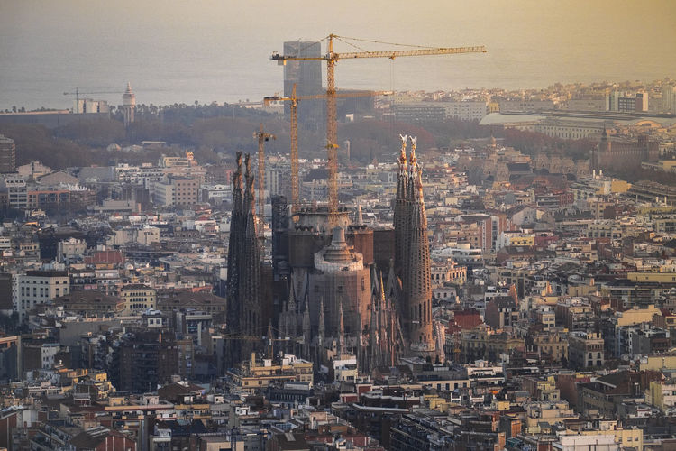 Under Construction Sagrada Familia Amidst Buildings In City During Sunset