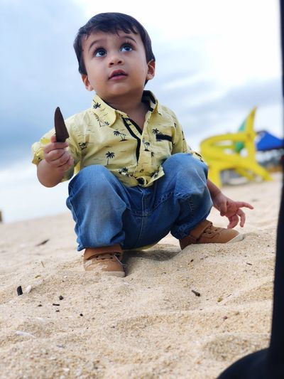 Thoughtful baby boy playing with sand at beach