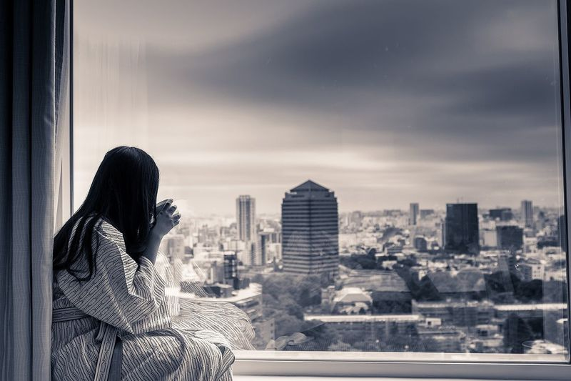 Woman drinking coffee while looking at cityscape through window