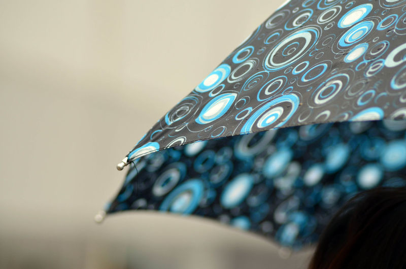 Close-Up Of Cropped Umbrella Against Blurred Background