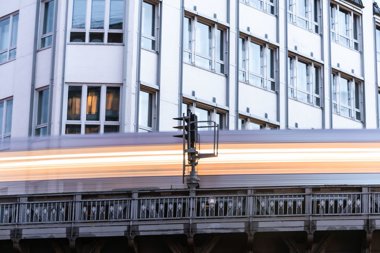 Low angle view of illuminated train moving by building in city