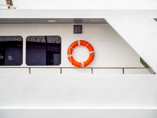Orange life buoy hanging on the white clean wall near the window glass in luxury travel boat with copy space. Architecture Built Structure No People Red White Color Safety Protection Building Exterior Security Orange Color Outdoors Wall - Building Feature Day Life Belt Window Shape Building Accidents And Disasters Geometric Shape Lifebuoy Lifering Yacht Hanging Orange Cruise