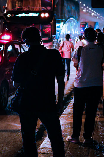 Rear view of people walking on street in city at night