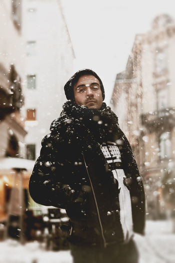 Portrait of man standing on street in city during winter