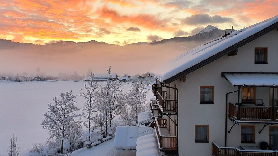 Snow covered buildings against sky during sunset