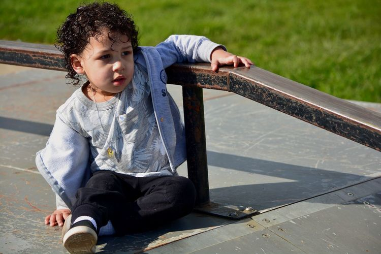 High Angle View Of Baby Boy Sitting By Railing At Skateboard Park