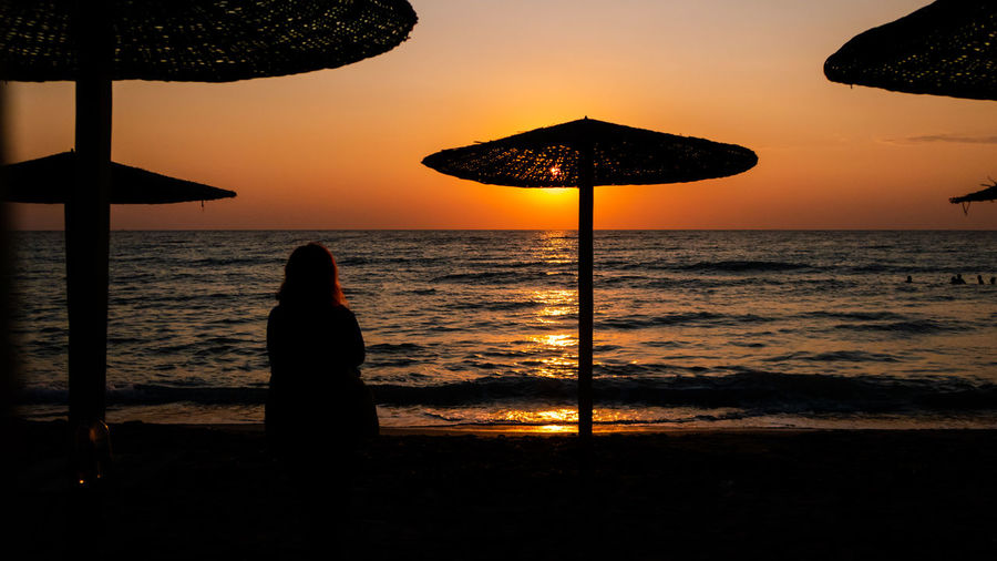 Silhouette woman looking at sea against sky during sunset