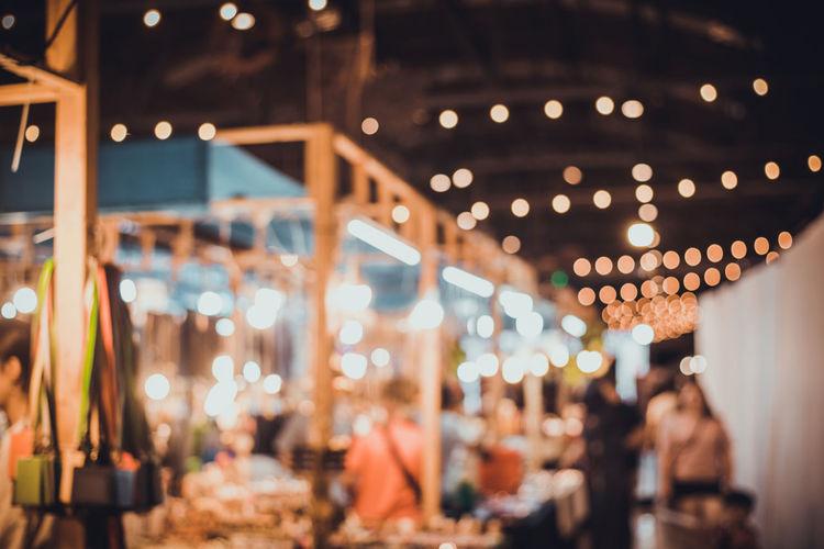 Defocused image of people at illuminated market during night