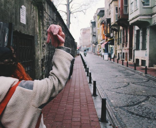 Cropped image of woman with hand raised standing on street amidst buildings