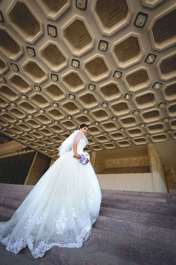 Low angle portrait of beautiful bride standing against patterned ceiling
