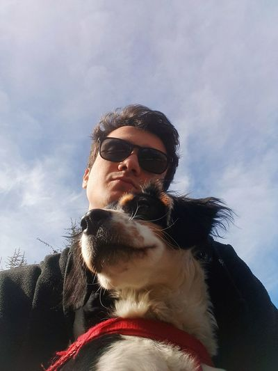 Portrait of man with dog against sky