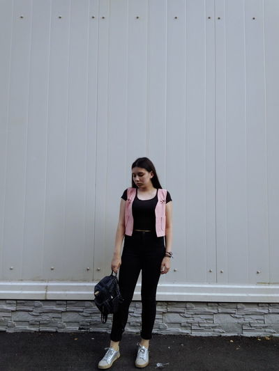 Full Length Of Young Woman With Backpack Standing Against Wall