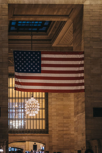 Large American flag inside Grand Central Terminal, a world-famous landmark and transportation hub in Midtown Manhattan, New York, USA. New York New York City USA United States Travel Tourism Flag Grand Central Terminal, Grand Central Station Stars And Stripes Patriotism Patriotic America Memorial Day Pride Independence Low Angle View No People National Icon NYC Proud Hanging Display City Train Station