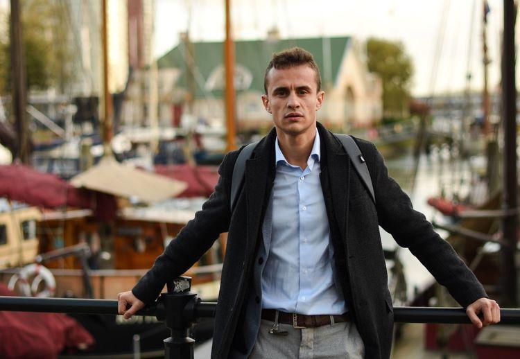 Portrait of businessman standing by railing against harbor