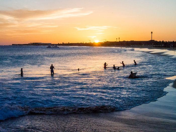 Sunset on beach, Santa Maria, Sal Island, Cabo Verde Water Sunset Sky Sea Waterfront Group Of People