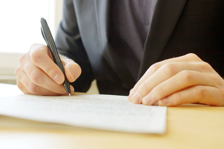 Midsection of businessman writing on paper