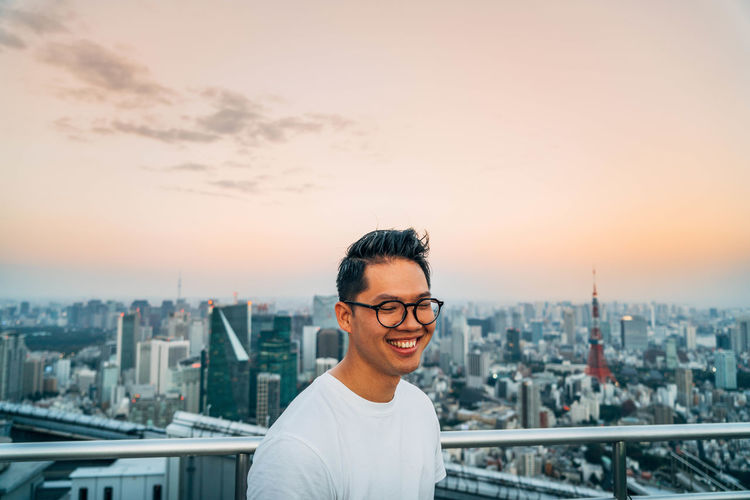 Smiling man standing at observation point against tokyo tower in city