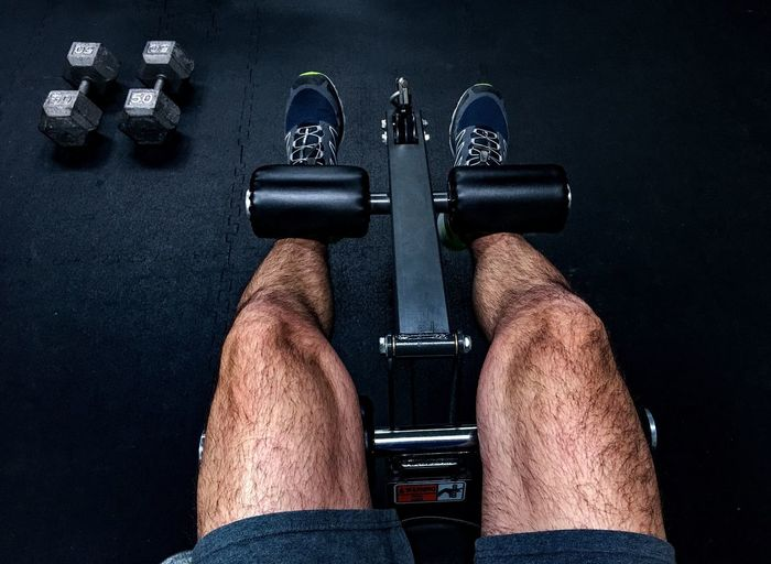 Low section of man lifting weights at gym