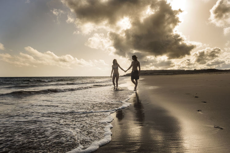 Man and woman holding hands at the beach during sunset