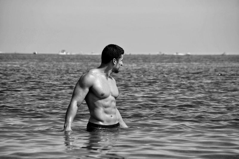 Shirtless man in sea against sky
