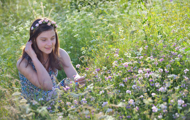 High angle view of teenage girl picking flowers